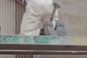 Ein Mitarbeiter der Löwen Restaurierung Müller OHG sorgt für die lotrechte Linienführung, während der andere mit der Schablone den Putz herauskämmt