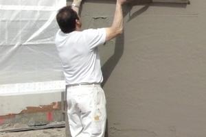 Abziehen des frisch auf die massiven Außenwände aufgetragenen KalkZementputzes mit dem Richtscheit