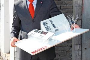 Sebastian Dresse, Geschäftsführer von Velux Deutschland, vor dem LichtAktiv Haus in Hamburg-Wilhelmsburg. In den Händen hält er das Modell des zukunftsweisenden Modernisierungsvorhabens<br />