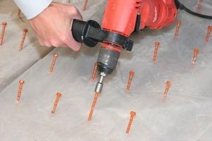 Arbeitsablauf zur statischen Ertüchtigung einer alten Holzbalkendecke mit einem Holz-Beton-Verbundsystem: Zunächst werden die Schubverbinderschrauben mit dem Akku-Schrauber eingedreht, dann die Bewehrungen verlegt und die Stahlstangen untereinander mit Draht verbunden. Schließlich wird der Aufbeton eingebracht und glatt abgezogen<br />