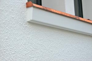 Der Putz in Kellenwurf-Optik mit einer 5 mm Körnung steht im Kontrast zu den feinen Fassadenprofilen