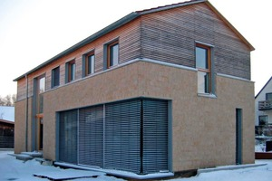 Die Fassade des Einfamilienhauses in Greißelbach gliedert sich in ein mit Betonwerkstein verblendetes Mauerwerk im Erdgeschoss sowie das mit Holzlatten verkleidete und in Holzleichtbauweise errichtete Obergeschoss<br />