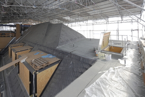Das neue Dach in seiner schützenden Einhausung. Im Vordergrund links die voll verglasten Dachgauben