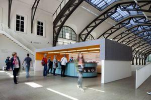 Seit Anfang Januar befindet sich am Eingang der historischen Halle ein aus Holzwolleakustikplatten halboffenen um die Rezeption erbauter Raum