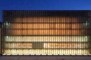 Durch die transluzente Fassade aus heiß verformtem Glas schimmert der Kubus des Lesesaals abends vom inneren Licht