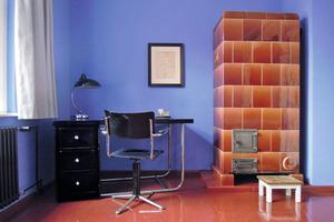 Kachelofen und Schreibtisch im blauen Schlafzimmer im Obergeschoss<br />