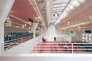 Der große Veranstaltungssaal wird durch eine geschwungene Decke aus Holzlamellen mit Tageslicht versorgt, das die darüber montierte Dachverglasung ins Gebäude lässt Foto: Benedikt Kraft