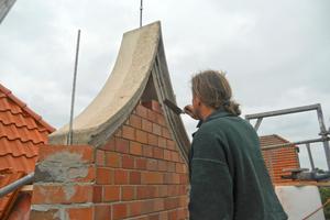 … und passt die schräg zugeschnittenen Ziegelsteine in das geschwungene Segment des Vorhangbogens ein