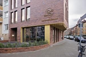 Innerhalb der Fassade setzen die Architekten auf ein Zusammenspiel der Materialien Backstein, Kupferblech und den bronzefarben eloxierten Teilen der Holz-Aluminium-Fenster