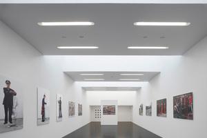 Der Blick in den Ausstellungsraum: Strahlendes Weiß trifft auf den dunkelgrauen, fast schwarzen Asphaltboden
