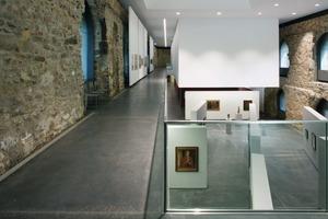 Blick in den Westflügel: In diesem Teil des riesigen Raumes blieben die schroffen Bruchsteinwände aus dem Mittelalter erhalten. Gut zu sehen: Die vom Dach abgehängte Ausstellungs-Box mit Erschließungsgalerie (links)<br />