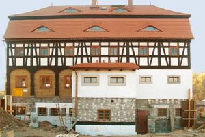 Der Wiederaufbau erfolgte auf einem massiv erbauten Erd- und Kellergeschoss als Gebäudesockel