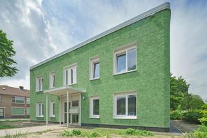 Die Fassade des sanierten Wohnhauses in Tilburg aus vorgefertigten, grünen Putzelementen ist an den Ecken gerundet