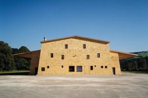 Die zum Dorf gerichtete Fassade springt aus dem Baukörper hervor und wurde in Anlehnung an die örtliche Bautradition verschindelt. Die 16x60cm großen Überformat-Schindeln fertigten die Zimmerleute aus Restholz