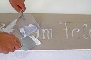 Die Schablone wird auf den Untergrund aufgelegt und mit Fassadenputz überarbeitet. Nach dem Abziehen der Schablone bildet sich der erhabene Schriftzug auf der Oberfläche ab