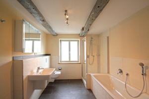 Auch im Bad sind im Obergeschoss die statisch ertüchtigten Deckenbalken zu sehen