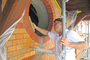 Nach der Verfugung des Ziegelmauerwerks im Schlämmverfahren wird der überschüssige Mörtel von der Fassade des Alten Bahnhofs in Warendorf mit dem feuchten Schwammbrett abgenommen