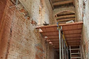 Ganz oben ist eine alte Holzbalkendecke zu sehen. In der Mitte die neue Ziegeldecke, während der Ausführung unterstützt von Montagestützen