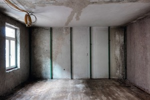 Links: Nach dem Aufstellen der Faulenzer (Eisenstangen zum Ausrichten und Herstellen der Dämmdicke) wurde an allen Innenflächen der Außenwände eine Dämmdicke von 8 cm im Mittel aufgesprüht