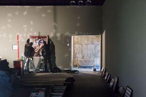 Hier werden an der montierten Ausstellungswand bereits zur Probe erste Kunstwerke gehängt