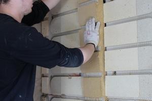 Montage einer Systemdämmplatte aus Holzfasern zwischen den Schamottsteinen
