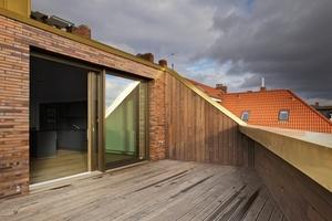 Die Deckschale der Hebe-Schiebe-Tür zur Dachterrasse ist passend zum Kupferblech der Dachdeckung wie die Holz-Aluminium-Fenster der Fassade in bronzefarben eloxiertem Aluminium ausgeführt