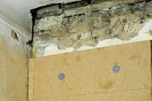 Daneben: Die hier zur Innendämmung verwendeten Weichfaserplatten werden mit Lehm vollflächig verklebt und zusätzlich mit Dübeln befestigt. Die Decke wurde bereits geöffnet, um die Dämmung bis in die Konstruktion ziehen zu können. So lassen sich Wärmebrücken vermeiden