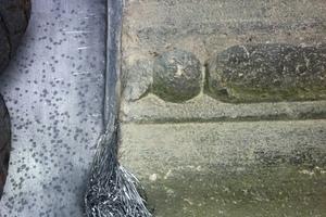 Einbringen von Bleiwolle in einer Fuge zwischen Metallblech und Mauerwerk Foto: Harald Handwerk Dachbau