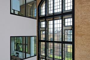 Blick vom Foyer auf die zum Kastenfenster ausgebildete historische Giebelfassade. Die Lichtöffnungen in dem eingezogenen Bürokubus sind Festverglasungen der Feuerwiderstandsklasse F 30 <br />