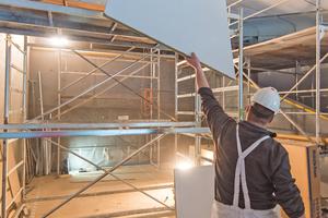 Zwischen die Enden der gebogenen Betonschalen schraubten die Handwerker Steinwolleplatten an die abgehängte Metallunterkonstruktion unter der Decke