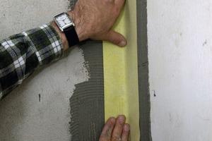 Nachdem der Handwerker den Fliesenkleber in den Ecken aufgebracht hat, wird das Dichtband eingebettet<br />