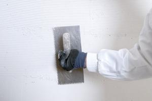 Für eine hochwertige Flächenspachtelung der Qualitätsstufe Q4 wird der Spachtel mit der Zahntraufel aufgetragen …<br />