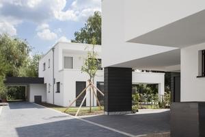 Die kubischen Baukörper scheinen durch die dunkle, anthrazitfarbene Stülpschalung an den Eingangsbereichen schier zu schweben