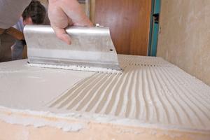 Für die Montage der Innendämmung wird iQ-Fix auf die Platten mit einer Zahnkelle auftragen