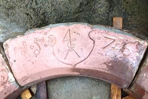 Zwischenbauphase nach Ausbau des Gewändes, auf dem Wappen und Jahreszahl sichtbar sind