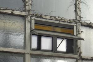 Detail der mit Riffelglas gefüllten Betonrasterfassade vor der Sanierung