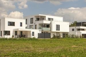 """Der Blick von Süden auf den Ost-West-Riegel der """"Bebauung Watzmannstraße/Hirschwiesenweg"""" mit zwei der vier Einfamilienhäusern (Einfamilienhäuser """"Ost"""" und """"Mitte"""") rechts, dem Mehrfamilienhaus """"Süd"""" und dem Einfamilienhaus """"Südwest"""" ganz links zeigt die gestaffelte Höhenentwicklung der Baukörper"""