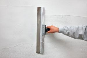 Bearbeitung des Putzes: Nach dem Aufspritzen wird die Fläche vorgeglättet, das Gewebe einbettet, der Oberputz aufgezogen und abschließend strukturiert<br />