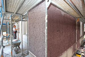 Die Fassade wirkt durch den starken Kontrast zwischen den in Trockenbauweise montierten und glatt grau beschichteten Zementbauplatten (links im Bild) und dem sehr groben Zupfputz auf dem WDVS der Massivbauwände (rechts im Bild) sehr lebendig<br />Foto: Knauf / Ralf Heikaus