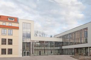 Die Neue Mitte Ichtershausen auf dem Gelände der ehemaligen Nadelfabrik: Links das denkmalgerecht sanierte Produktionsgebäude D, rechts daran anschließend der auf Stützen ruhende Mehrzwecksaal Foto: Sigma Plan