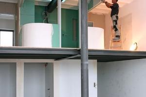 Montage des Badezimmers aus gebogenen Trockenbauwänden in einer der Loftwohnungen. Wie der Raum fast fertig gestellt aussieht, zeigt die folgende Seite