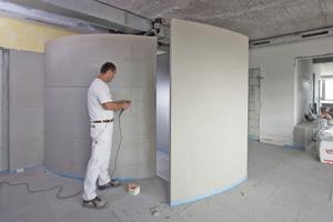 Links: Beim Bau der Duschkabinen eines Freiburger Fitness-Centers  waren engen Radien von 3 m und 2,50 m vorgesehenen. Nach Montage der Unterkonstruktion im Abstand von 20 cm wurden die Wandbauplatten in 20 cm breite Streifen  geschnitten und angebracht Foto: Fermacell