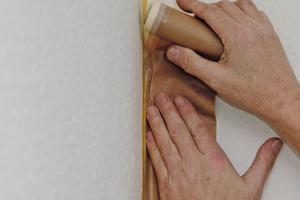 Die angrenzenden Flächen sollten mit einem Abdeckpapier oder einer PE-HD Folie geschützt werden. Am besten geht das mit integriertem Klebeband