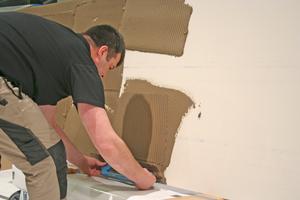 """Ein Handwerker zieht Klebemörtel auf die Rückseite einer Fliese auf<span class=""""bildnachweis"""">Fotos: Stephan Thomas</span>"""