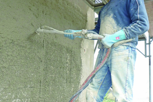 Auftrag von Vorspritzmörtel und Sanierputz mit der Putzmaschine an der Fassade