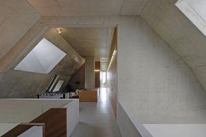 Wohnen in der Betonskulptur: Blick in den Flur mit angrenzenden Schlafzimmern im Dachgeschoss Foto: Robert Mehl