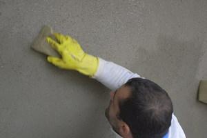 Letzter Arbeitsschritt an der Putzfassade: Abwaschen mit dem Schwamm