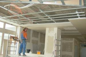 Unter der Decke erhielten abgehängte Unterkonstruktionen eine Beplankung mit Bauplatten RB 12,5 mm. Einzelne Felder statteten die Handwerker mit akustisch wirksamen Lochplatten aus<br />