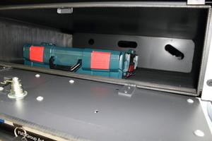 In dem abschließbaren Fach unter der Ladefläche lassen sich Werkzeug oder auch Besen und Schaufel mitführen – durch die Löcher in der Rückwand des Faches können dann die Stiele gesteckt werden
