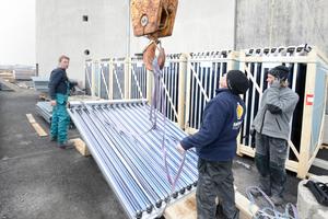 Die Solarmodule werden von den Handwerkern an den Kran gehängt ...<br />